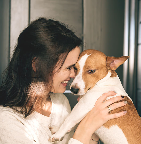 Young beautiful smiling woman hugging her dog at home
